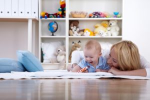 Mother lying on floor with smiling baby in playroom