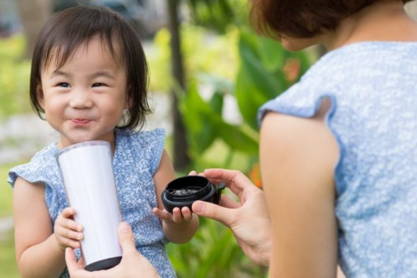 girl drinking from cup with mom outside