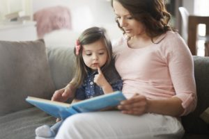 Mom and daughter reading together and talking