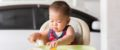 baby picking finger foods off high chair