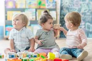Three toddlers playing with blocks at daycare