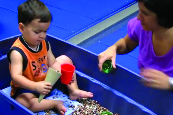 boy playing with sensory bin during occupational therapy