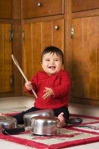 baby playing with pots and wooden spoon