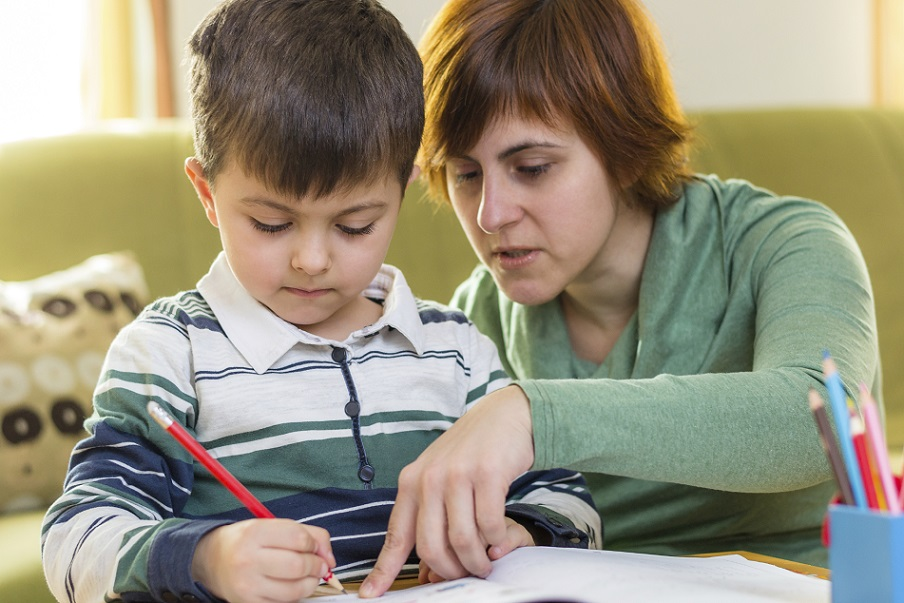 Boy doing homework with mom's help