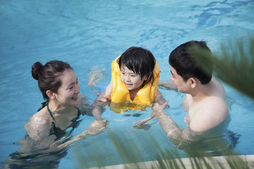 family swimming in pool