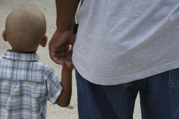 A young boy holding his dad's hand