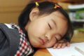 young girl sleeping at school desk