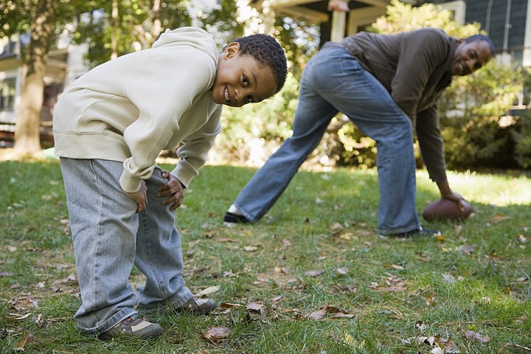 father and son playing football in yard on a fall day