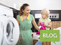Smiling mother with little daughter loading clothes into washing machine at home