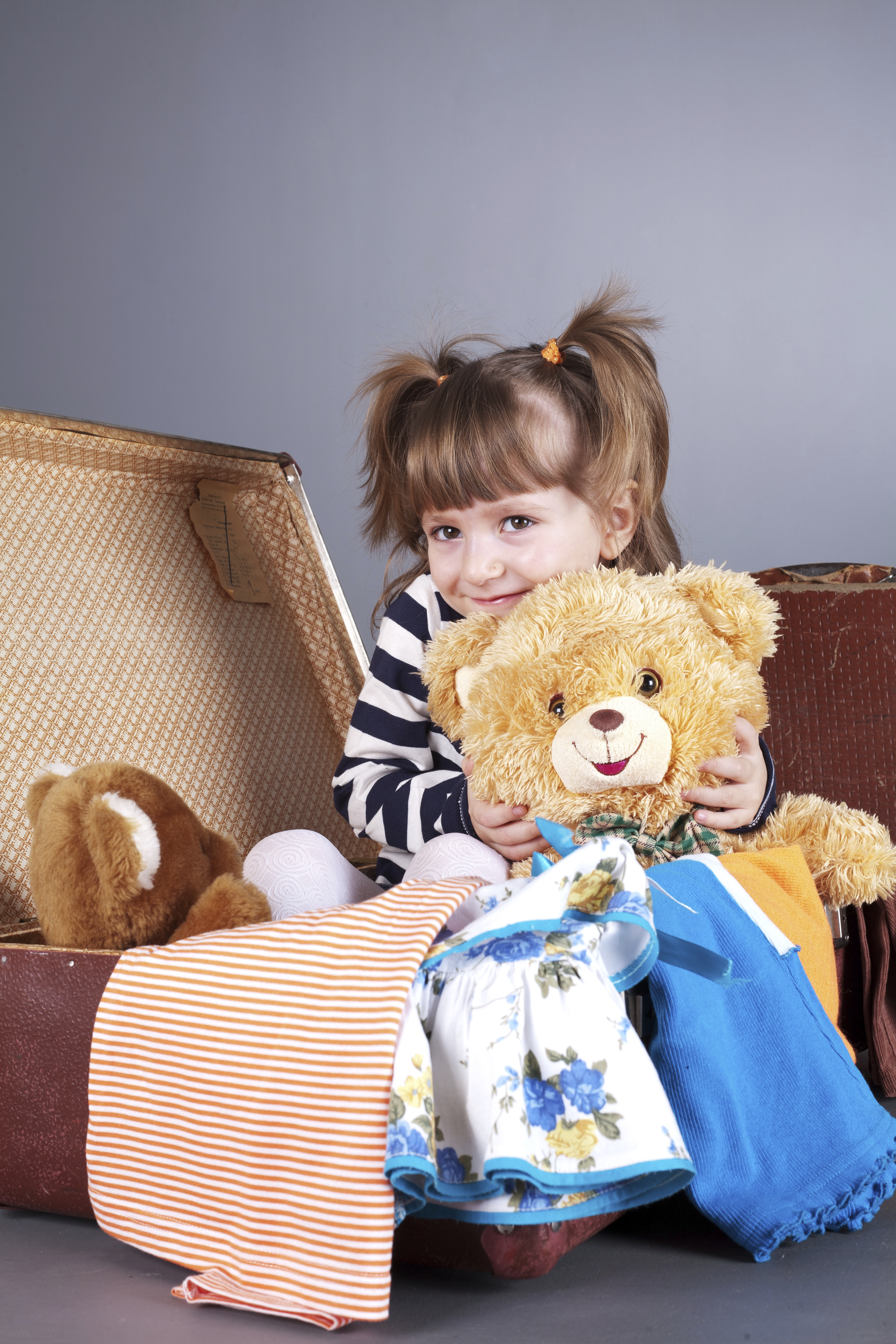 four-year girl joyfully sits in an old suitcase with toys and clothes