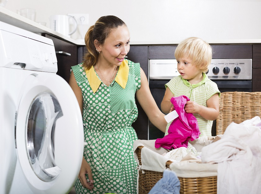 mom and young child doing laundry together