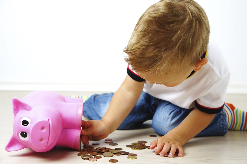 young boy counting coins from piggy bank