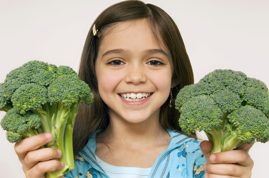 young girl smiling and holding broccoli