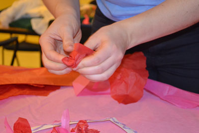 using fine motor skills to pinch tissue paper for craft