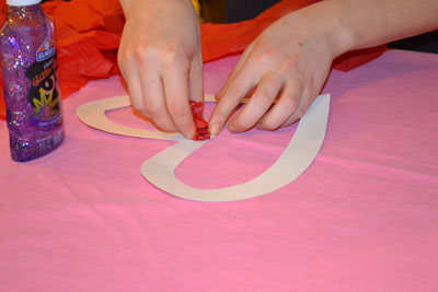 gluing tissue paper to heart for valentine's day craft
