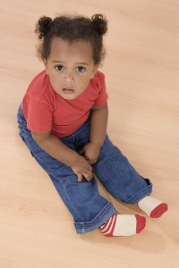 Toddler sitting with legs out in front