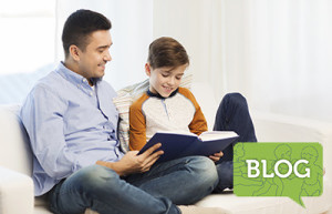 boy sitting with his father reading a book