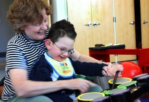 boy with glasses playing drums with occupational therapist