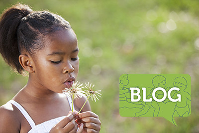 young girl outside blowing dandelion