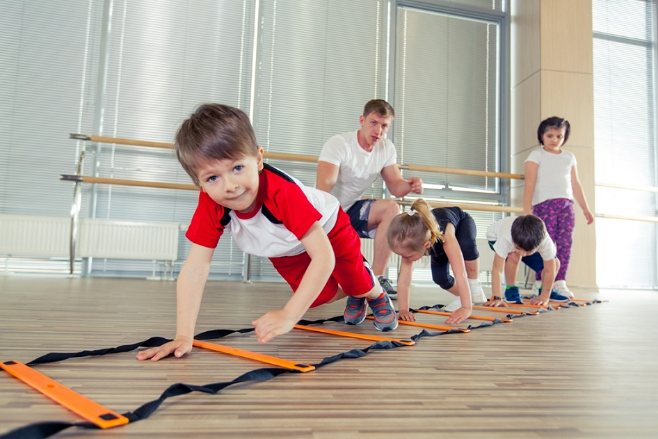 Kids crawling on ladder in gym