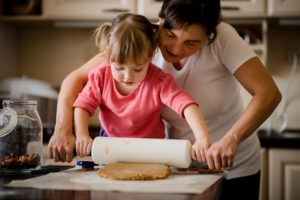 mother and daughter baking together and using rolling pin