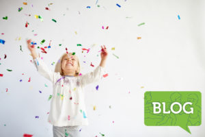 excited young girl throwing confetti in white room