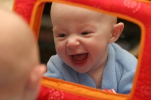 baby boy laughing and looking in mirror