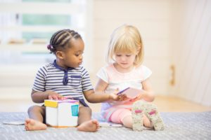 two_girls_sharing_book_during_play