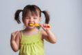 young girl with pigtails brushing her teeth