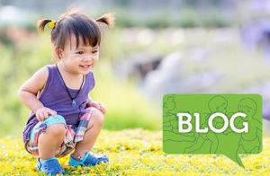 little girl bending down outside in grass