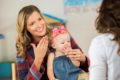 mom playing with daughter and teaching baby sign language