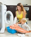 toddler helping mom with laundry