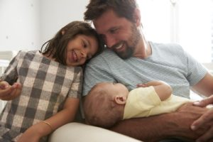 Father With Daughter And Newborn Son In Nursery