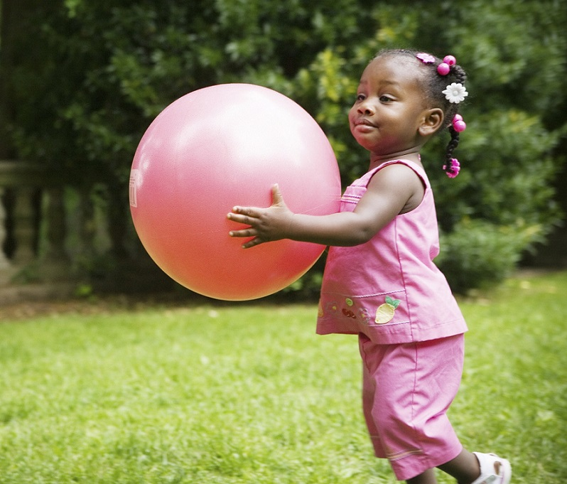 young girl playing with pink ball outside