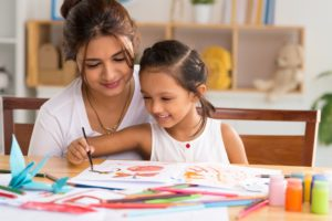young girl drawing a picture with her mom