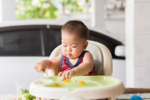 Baby eating with spoon in high chair
