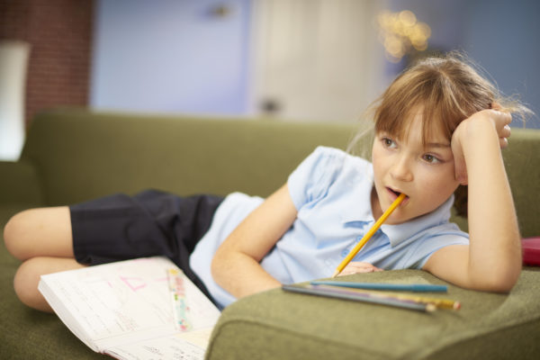 Girl watching television while doing homework