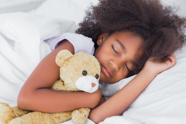Cute little girl sleeping in bed cuddling teddy bear