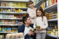 Happy smiling parents with little girl buying tinned