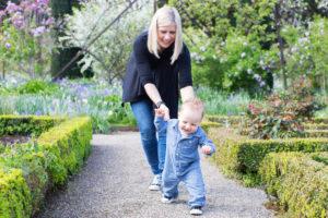 mom chasing baby through garden