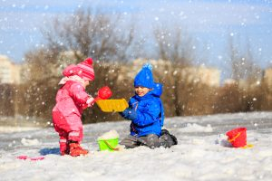 two_children_playing_with_shovels_in_the_snow