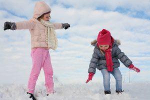 two_girls_walking_through_the_snow