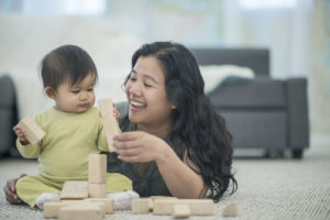 mom and infant stacking wood blocks