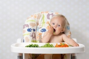 baby_in_high_chair_holding_vegetable