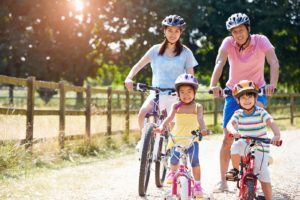 family_riding_bikes_together_on_sunny_day