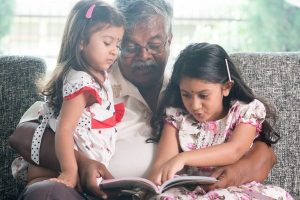 grandpa and two girls reading book together