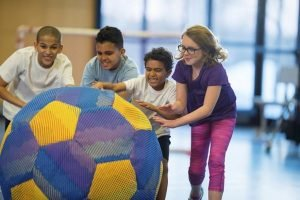 kids rolling giant ball in gym