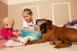 little_girl_and_baby_playing_dress_up_with_dog