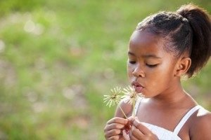 young_girl_blowing_dandelion