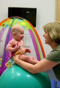 smiling therapist with baby sitting on ball